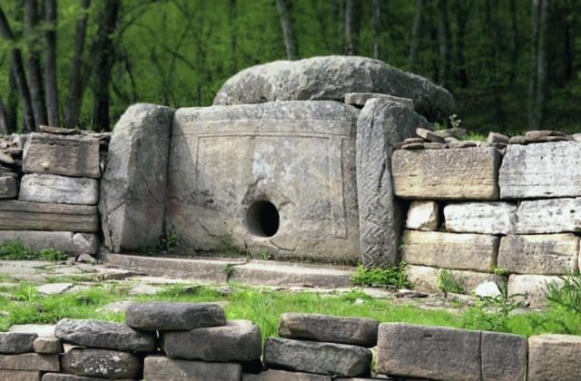 Кавказский дольмен окружен каменной стеной.